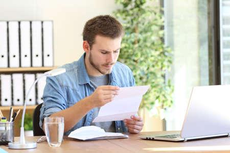 Foto de Serious entrepreneur working and reading a letter in a desktop at workplace - Imagen libre de derechos