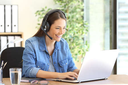 Photo for Freelance operator working in telemarketing on line with headsets and a laptop in a desktop at office - Royalty Free Image