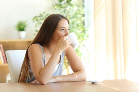 Photo for Portrait of a girl sitting on a chair drinking coffee and looking outside through a window at home with a warm natural light - Royalty Free Image
