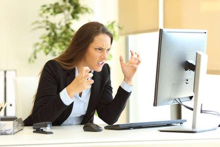Photo pour Furious businesswoman wearing suit using a desktop computer on line beside a window at office - image libre de droit