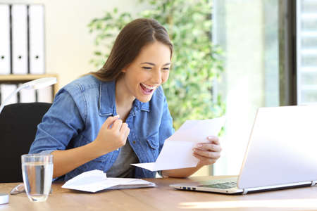 Photo for Excited casual entrepreneur girl reading good news in a letter in a desktop at office - Royalty Free Image