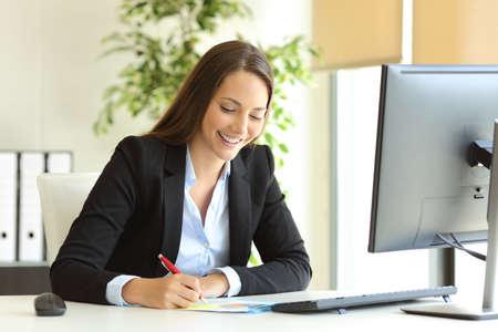 Photo pour Businesswoman wearing suit working handwriting notes in a desktop at office - image libre de droit