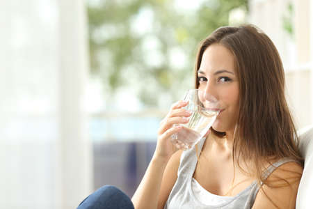 Foto de Woman drinking water at home and looking at you sitting on a couch in the living room at home - Imagen libre de derechos