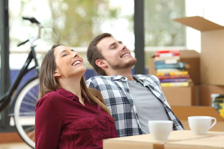 Photo pour Happy couple sitting on the floor of the living room relaxing together while moving house with a window in the background - image libre de droit