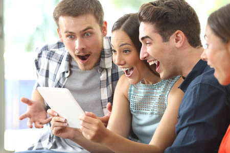 Photo for Four amazed friends watching media content together in a tablet sitting on a sofa in the living room at home - Royalty Free Image