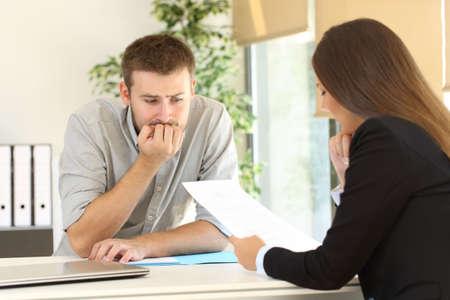 Foto de Nervous man looking how the interviewer is reading his resume during a job interview - Imagen libre de derechos