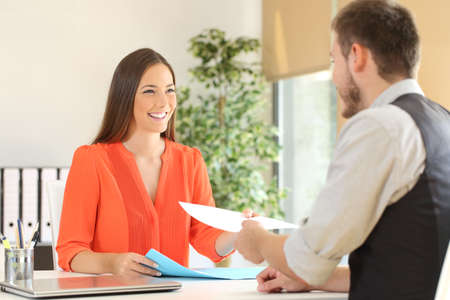 Photo for Woman giving a resume to the interviewer in a job interview - Royalty Free Image
