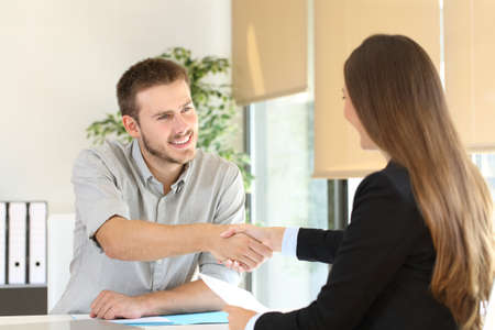 Photo for Happy employee and boss handshaking after a successful job interview at office - Royalty Free Image