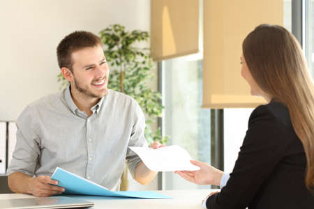 Foto de Man giving a resume to the interviewer in a job interview in a desktop at office - Imagen libre de derechos