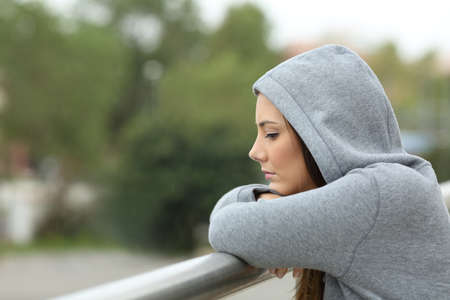 Photo pour Side view of a sad single teenager looking down in a balcony of her house in a rainy day - image libre de droit