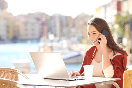 Photo for Girl using a laptop on line and calling customer service on mobile phone in a bar terrace with a port in the background - Royalty Free Image