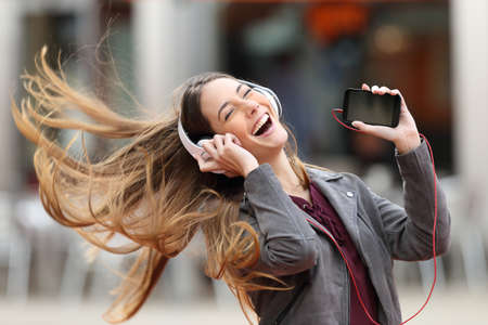 Foto de Excited girl dancing and listening music with headphones and smart phone in the street with hair moving - Imagen libre de derechos