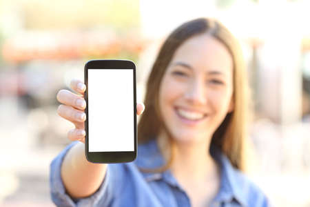 Photo pour Front view of a happy girl showing a blank smart phone display and looking to the camera in the street - image libre de droit