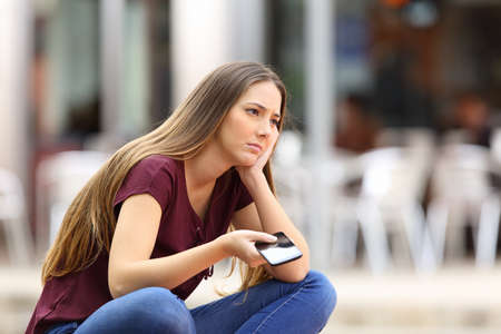 Foto de Sad girl waiting for a mobile phone call or message from her boyfriend sitting in a bench outside in the street with an urban background - Imagen libre de derechos
