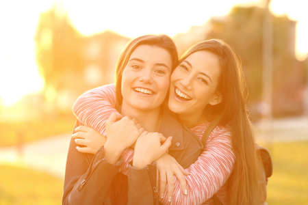 Photo for Front view portrait of two happy friends laughing and posing looking at you in the street at sunset with a warm light in the background - Royalty Free Image