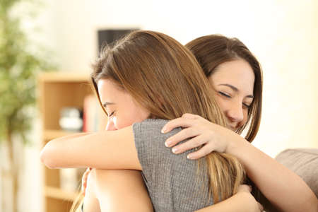 Photo pour Happy girls embracing at home sitting on a couch in the living room at home - image libre de droit