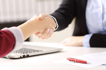 Photo for Close up of two businesswomen hands handshaking after closing a deal and signing contract in a desk with an office background - Royalty Free Image