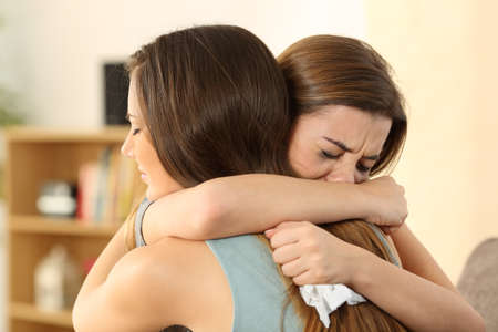 Foto de Girl embracing to comfort to her sad best friend after break up sitting on a couch in the living room at home - Imagen libre de derechos