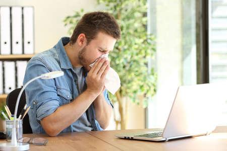 Foto de Side view of an ill entrepreneur sneezing in a wipe at office near a window - Imagen libre de derechos