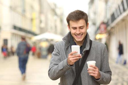 Foto de Front view portrait of a businessman walking towards camera and using a smart phone in the street in winter - Imagen libre de derechos
