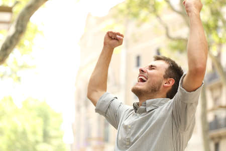 Photo for Portrait of an excited man raising arms in the street with buildings in the background - Royalty Free Image