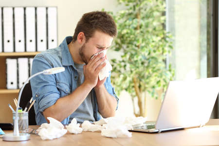 Foto de Portrait of a sick entrepreneur blowing in a wipe at office with a lot of used wipes on the desk - Imagen libre de derechos