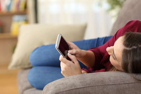 Photo pour Close up of a relaxed girl using a smart phone lying on a sofa in the living room at home with a cozy background - image libre de droit