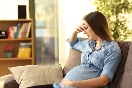 Worried pregnant woman sitting on a couch in the living room at home
