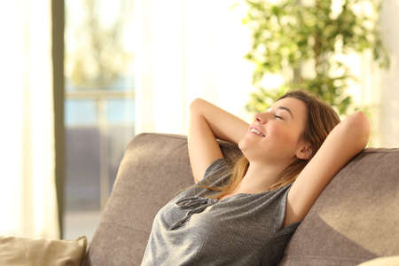 Foto de Portrait of a girl relaxing on a sofa after work at home sitting on a sofa in the living room at home with a warm light of sunset - Imagen libre de derechos
