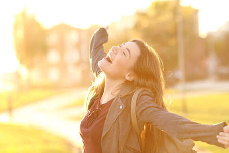 Photo for Portrait of an excited teenager girl raising arms and laughing in the street at sunset with a warm light in the background - Royalty Free Image