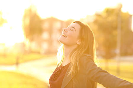 Photo pour Back light portrait of a happy single teen girl breathing fresh air at sunset in a park with a warm yellow light and urban background - image libre de droit