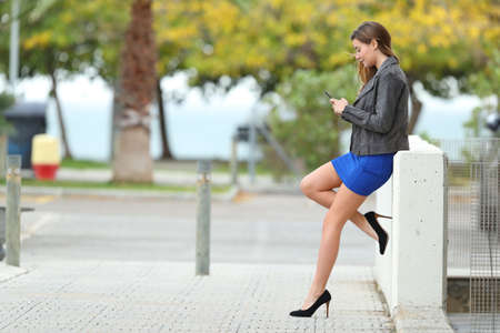 Photo pour Side view of a full body of a fashion girl with long perfect legs using phone in the street - image libre de droit