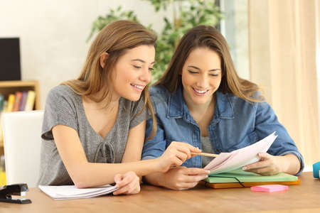 Photo pour Two students doing homework together and helping each other sitting in a table at home with a homey background - image libre de droit