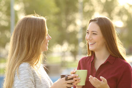Foto de Two happy friends talking holding coffe mug outdoors in a park with a green background at sunset with a warm back light - Imagen libre de derechos