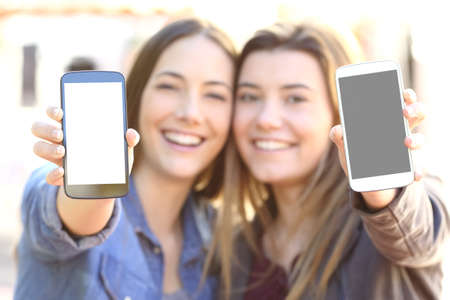 Photo pour Front view of two happy friends showing both blank smart phone screens in the street with a blur background - image libre de droit