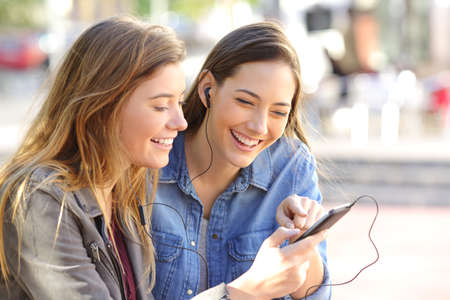 Foto de Two happy friends sharing a phone to listen music on line together in the street with an urban background - Imagen libre de derechos