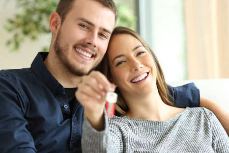 Foto de Happy couple of owners showing house keys to the camera sitting on a sofa in the living room at home - Imagen libre de derechos