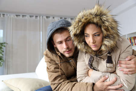 Photo pour Cold home with an angry couple warmly clothed hugging sitting on a sofa in the living room - image libre de droit