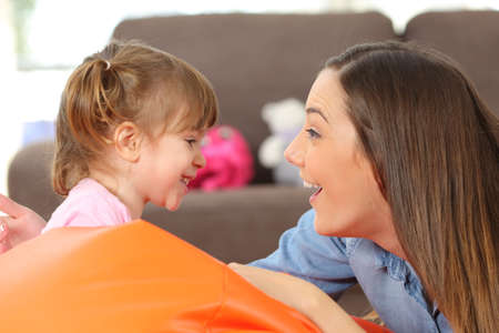 Foto de Side view portrait of a happy mother and 2 years baby daughter facing and joking in the living room at home - Imagen libre de derechos