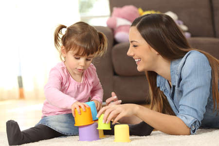 Photo pour Happy mother and concentrated baby daughter playing with toys together sitting on the floor of the living room at home - image libre de droit