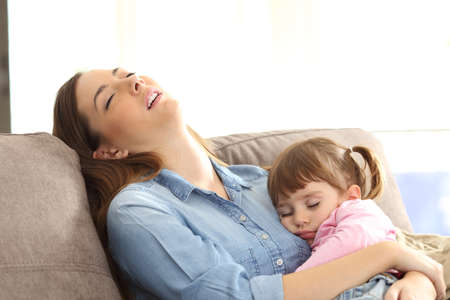 Photo for Tired mother sleeping embracing to her asleep baby daughter sitting on a sofa at home - Royalty Free Image
