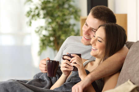 Photo pour Happy couple relaxing and drinking tea covered with a blanket sitting on a sofa in the living room in a cozy house interior - image libre de droit