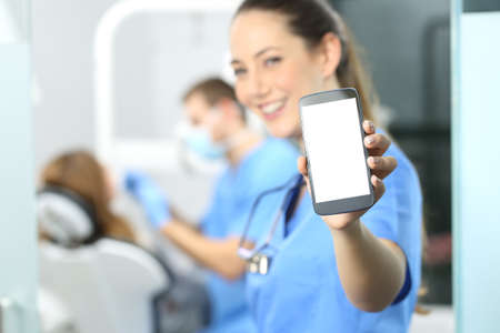Photo pour Stomatologist showing phone screen and looking at you in a dentist office interior with a doctor working in the background - image libre de droit