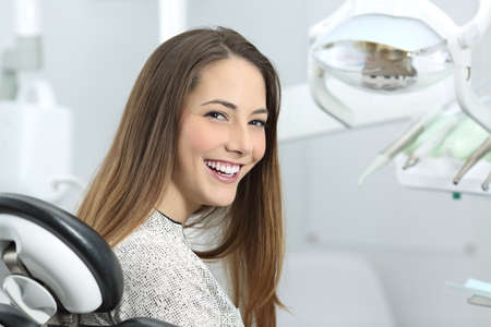 Photo pour Satisfied dentist patient showing her perfect smile after treatment in a clinic box with medical equipment in the background - image libre de droit