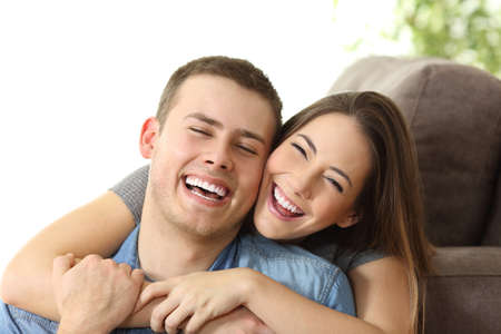 Photo pour Happy couple with perfect white smile posing and looking at camera on a couch at home - image libre de droit