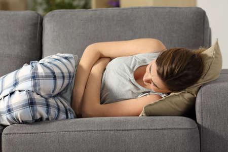 Foto de Teen suffering belly pms symptoms lying on a sofa in the living room at home - Imagen libre de derechos
