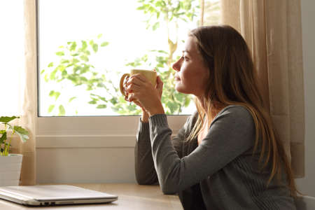 Foto de Side view of a relaxed woman looking through a window sitting in a table and holding a cup of coffee at home - Imagen libre de derechos