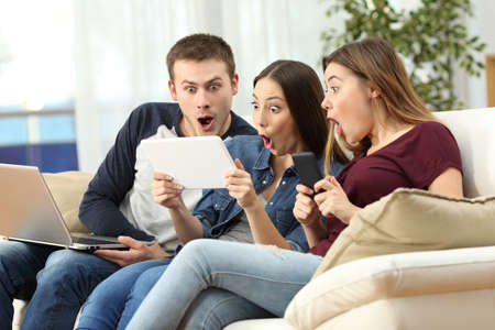 Foto de Three amazed friends on line with multiple devices sitting on a sofa in the living room in a house interior - Imagen libre de derechos