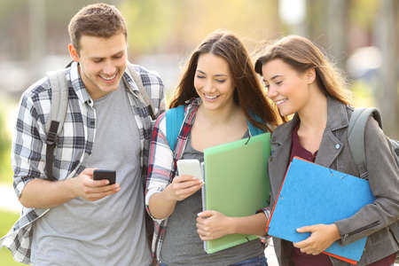 Photo pour Three happy students checking smart phones outdoors in an university campus - image libre de droit