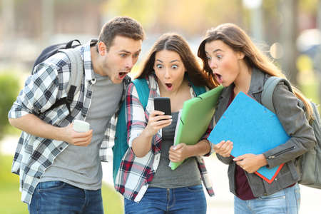 Photo pour Three amazed students checking on line content on a smart phone in the street - image libre de droit